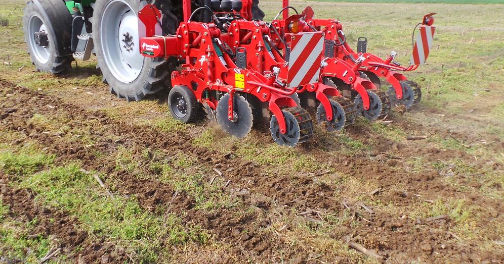 Il Kverneland Kultistrip in azione su un terreno coperto da residui colturali per preparare le strisce lavorate dove la seminatrice deporrà il seme.