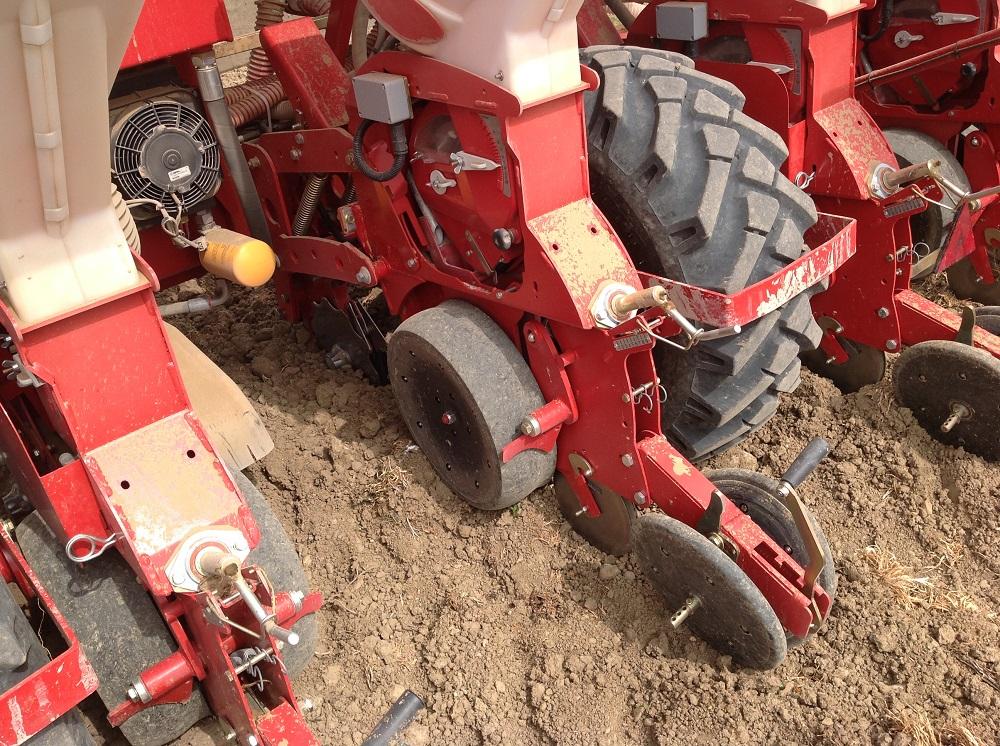 """In questa foto si nota il martinetto a vite per regolare comodamente la profondità di semina determinata dalle due ruote gommate e anche l'elemento che regola l'inclinazione delle due ruote a """"V"""" coprisolco. Notare anche lo pneumatico di trasporto/lavoro disponibile in differenti misure."""
